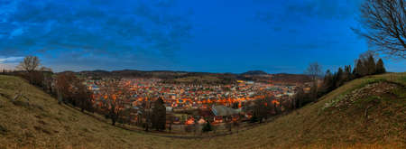 The illuminated city Albstadt at the recreation area of the Swabian Alb in panoramic view in the evening mood. 写真素材