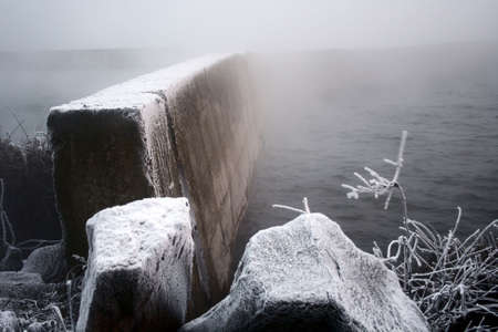 evaporating: stone wall rising from water disapearing in fog