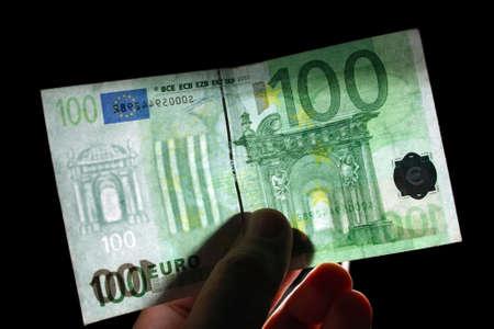 checking watermark 100 euro isolated on black photo