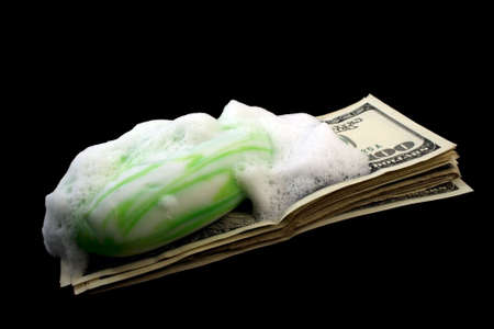 dirty money with soap and foam isolated on black photo
