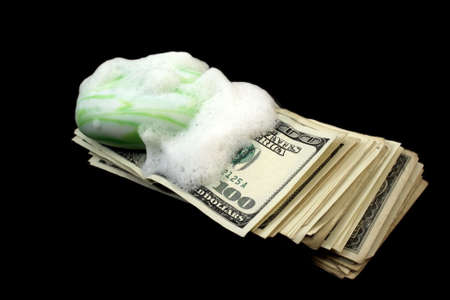 money laundering: dirty money with soap and foam isolated on black