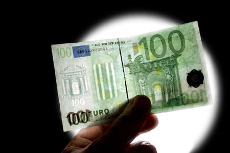 vals geld: controle van watermerk 100 euro geïsoleerd op zwart met wit licht Stockfoto