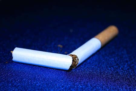 habitual: broken cigarette on blue table-cloth
