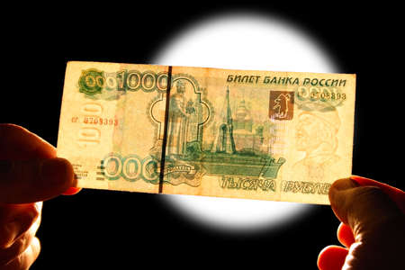 checking watermark 1000 russian rubles over white lamp isolated on black photo