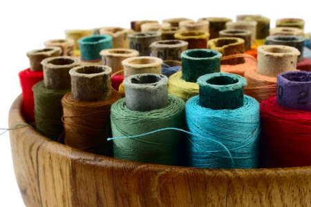 coloured threads in wooden plate isolated on white photo