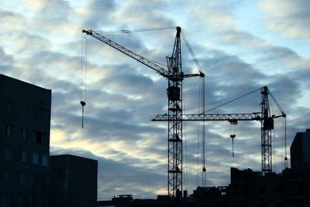 erect: couple lifting cranes and buildings over evening sky and clouds