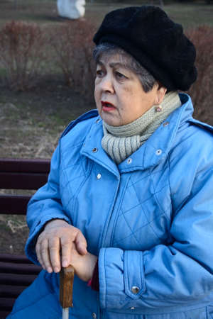 confide: elderly woman confide story of her life sitting on bench Stock Photo