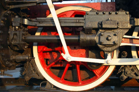 single red wheel of old steam train with connecting rod photo