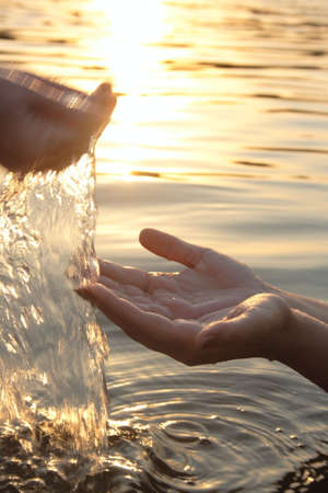woman hands giving you water on sunset Stock Photo