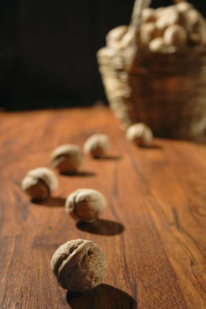 path from nuts on wooden surface loading to basket with nuts