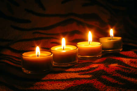 raw candles  on dark tiger striped surface photo
