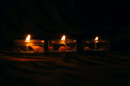 three decorative candles on dark striped background  photo
