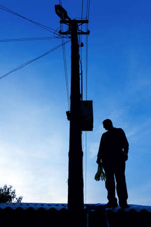 Electrician on the roof looking around before repairs power line Stock Photo
