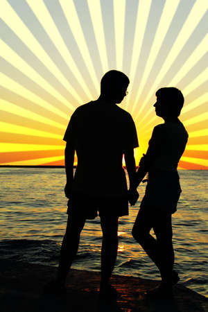 romantic yong man and woman looking at each other at sunset photo