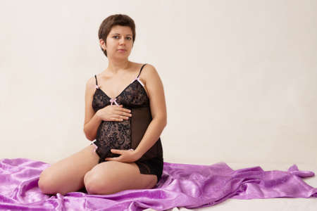 Beautiful pregnant woman seated on the floor with purple fabric photo