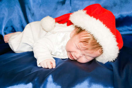 baby wearing a red and white Christmas Santa hat and crying photo