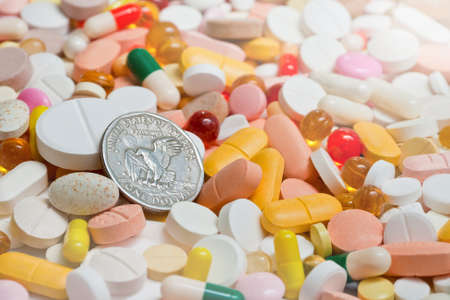Lot of pills and usa one dollar coin over them. Focus on coin. photo