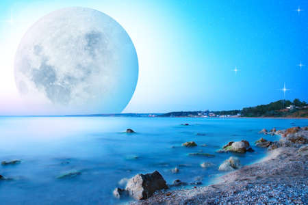 Abstract sunset landscape with big moon on seacost. Stock Photo