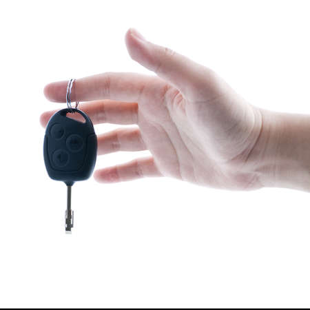 Womans hand giving key from modern car. Isolated on white background.