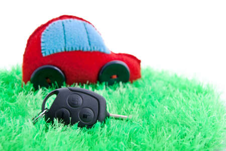 Clean ecology concept car and key for it on green grass. Focus on the key. Isolated on white. photo