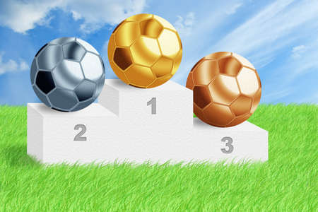Golden, silver and bronze football balls on podium among green grass with blue cloudy sky. photo