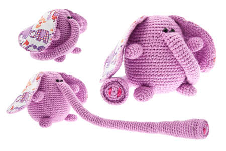 Three pink elephants with long trunk. Crochet toys. Isolated on white background. Stock Photo