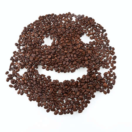 Coffee grains arranged in smiley. Isolated on white background. photo