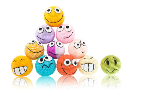 Lot of handmade colored smileys in piramide and one of them with sad face near it. Isolated on white background.