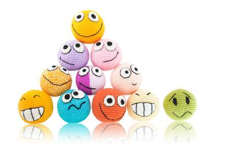 Lot von handgemachten farbigen Smileys in piramide und einer von ihnen mit traurigem Gesicht in der Nähe davon. Isoliert auf weißem Hintergrund. Standard-Bild - 13175679