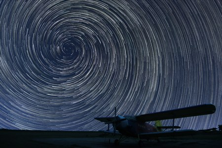 Beautiful night sky, Spiral Star trails over small airport lonely airplane. Vortex Star trails.