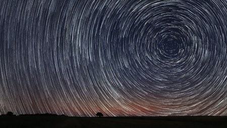 Beautiful Star Trails over filed with lonely tree. Beautiful night sky. Stock Photo