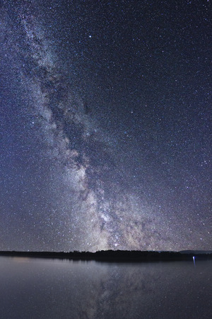 Milky Way galaxy beautiful night sky reflection on water. Banco de Imagens