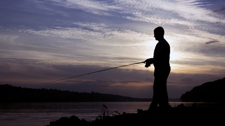 Silhouet van Fisherman op zonsondergang, Visser Casting Stockfoto - 46721588
