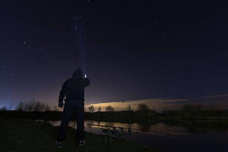 paciencia: Pescador en la noche estrellada, que señala a Orión, el cazador de la constelación, la paciencia. Foto de archivo