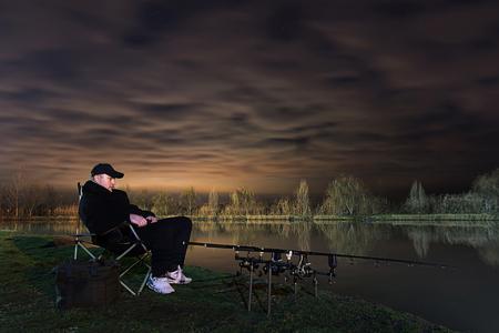 paciencia: Pescador en la noche hermosa, sentándose en la silla mirando en las barras, la paciencia Hermoso nubes.