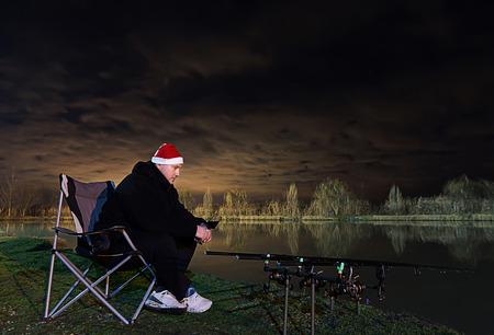 paciencia: Pescador con el sombrero de Santa, la vid en la mano, sentado en la silla mirando en las barras, paciencia Hermosa clodudscape en la noche Foto de archivo