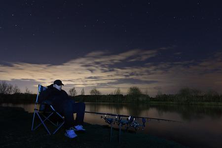 paciencia: Pescador en la noche estrellada, sentado en la silla mirando en las barras, la paciencia Foto de archivo