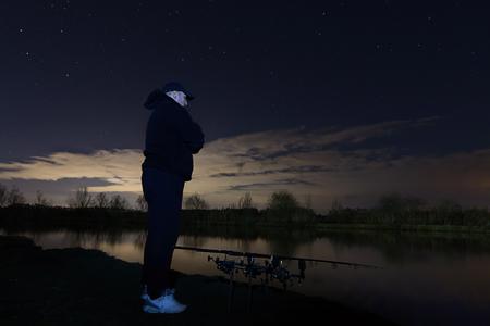 paciencia: Pescador en la noche estrellada, de pie y mirando en las barras, la paciencia.