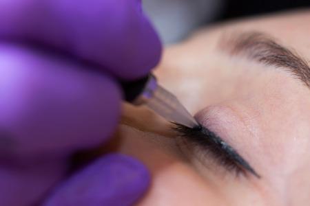 mujer maquillandose: Cosmetólogo la aplicación de maquillaje permanente en los ojos de enfoque selectivo y la profundidad de campo