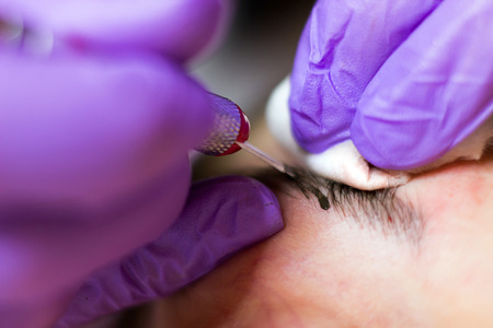 Cosmetologist applying permanent makeup on eyebrows Selective focus and shallow Depth of field