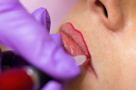 mujer maquillandose: Cosmetólogo la aplicación de maquillaje permanente en los labios de enfoque selectivo y la profundidad de campo
