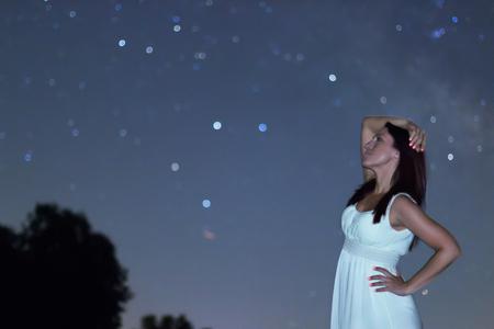 starry night: Woman in white long dress under starry night. Woman looking to starry night. Woman under night sky, Defocused night sky. Stock Photo