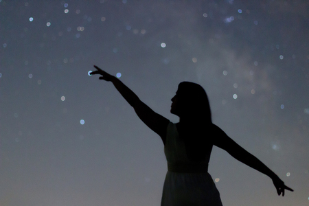 Silhouette of a dancing woman pointing in night sky. Woman Silhouette under starry night, Defocused Milky Way galaxy.