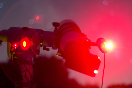 starry night: Astrophotography setup in clear night. Refractor type telescope. Telescope in real starry night. Blurred night. Red astronomy lights
