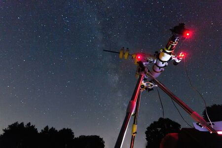 astrophotography: Astrophotography setup in clear night. Refractor type telescope. Telescope in real starry night. Blurred night. Red astronomy lights
