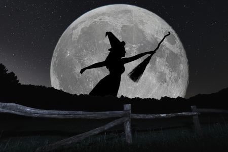 Halloween witch silhouette flying with broomstick. Full Moon. Archivio Fotografico