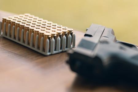 casings: Gun with bullets. Handgun box with new ammunition.