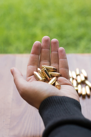 Hand with 9mm bullets. Hand holding bullets.