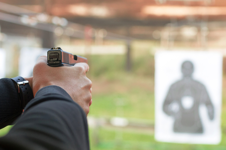Shooting with a pistol. Man aiming pistol in shooting range. Banco de Imagens