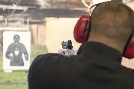 Shooting with a pistol. Man aiming pistol in shooting range. Stockfoto